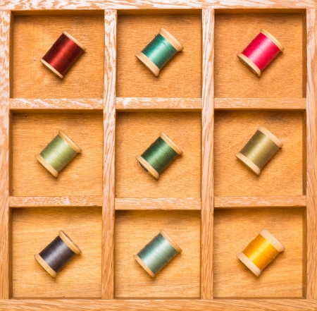 Bright thread on spools in wooden shadow box photo