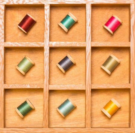 Thread on spools in wooden shadow box photo