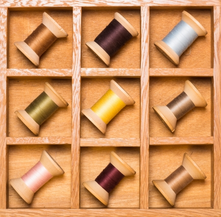 Wooden shadow box with wooden thread spools arranged by color