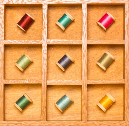 Colorful thread on spools in wooden shadow box