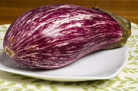 Colorful striped purple eggplant on white plate Reklamní fotografie