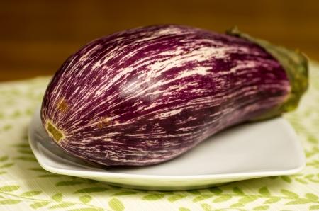 Purple striped eggplant on white plate
