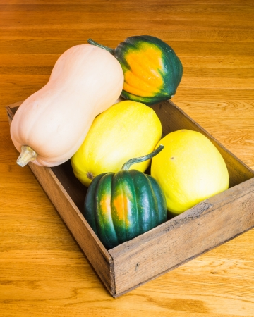 A wooden box of freshly harvested winter squash