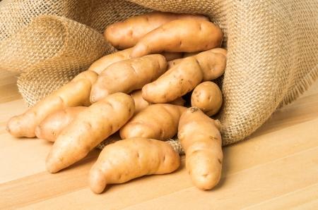 fingerling: Burlap of fingerling potatoes spilling onto the table Stock Photo