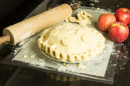 An apple pie with decorated crust apples and rolling pin Banco de Imagens