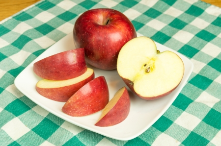 winesap apple: Winesap apple sliced on white plate
