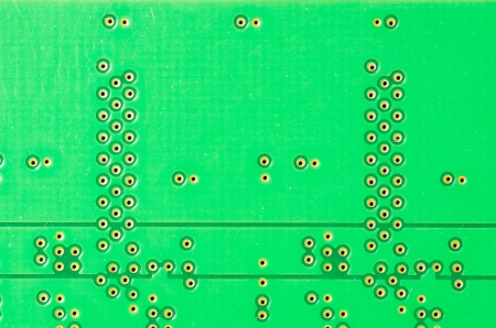 A closeup of a printed circuit board with solder points photo