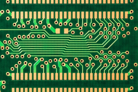 A closeup of a printed circuit board with gold traces photo