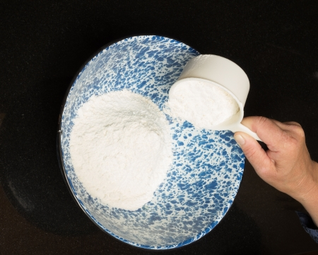 A baker measuring flour into a bowl to make biscuits Stock Photo