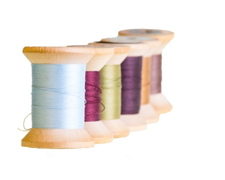 Row of wooden sewing thread spools Stock Photo