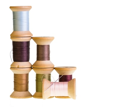 Wooden spools of sewing thread with a needle isolated on white