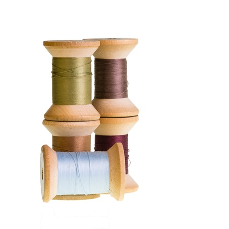 Wooden spools of sewing thread isolated on white Stock Photo