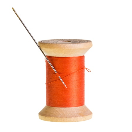 Spool of orange thread with a needle isolated