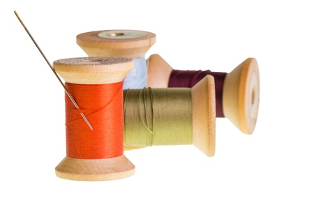 Four spools of sewing thread with a needle