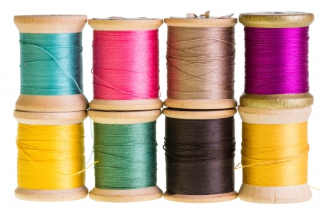 Eight spools of sewing thread isolated on white
