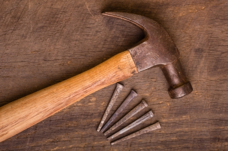 A hammer and nails on an old wooden board Stock Photo - 17453290