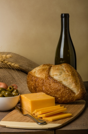 A still life with sausage cheese olives wine bottle and bread on a cutting board photo