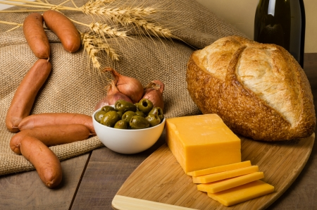 A still life with sausage cheese olives and bread on a cutting board photo