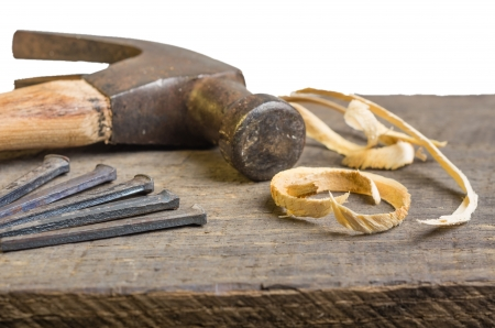 A hammer and nails on a wood board with sawdust shavings Stock Photo - 17571684