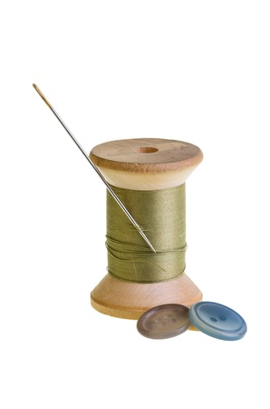 A spool of sewing thread with needle and buttons Stock Photo