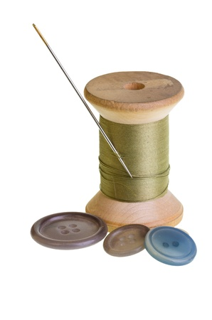 A spool of green thread with needle and buttons
