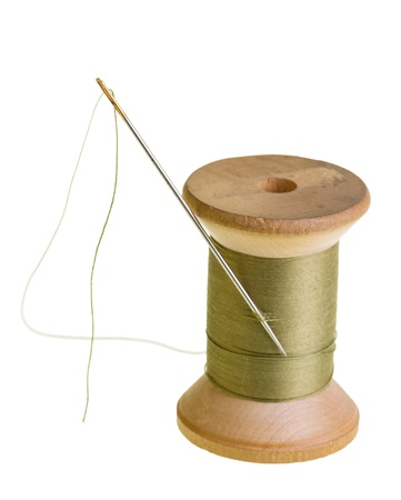 A spool of green sewing thread with a needle Stock Photo