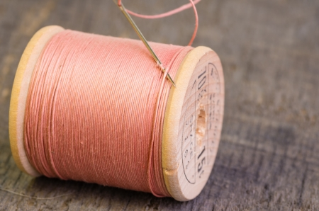 A spool of sewing thread and a needle Stock Photo
