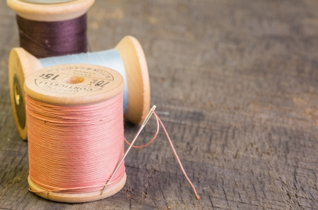 Spools of sewing thread on wooden table with a needle