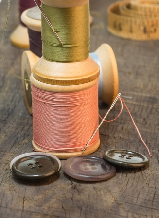 Needles and sewing thread on spools with buttons