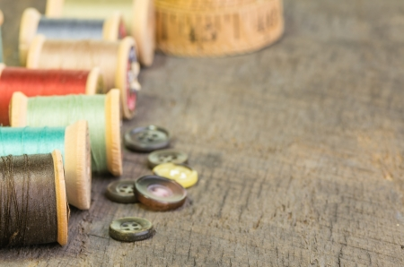 A row of sewing thread spools with buttons Stock Photo