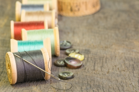 Sewing thread on spools with needle and buttons
