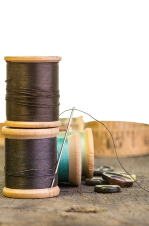 Stack of sewing thread with needle and buttons