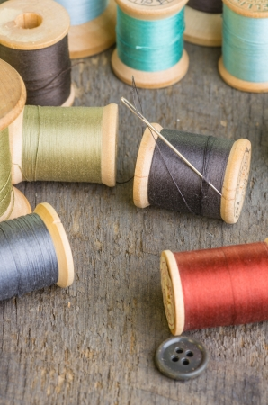 Spools of sewing thread on table with a needle