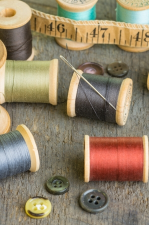Measuring tape and spools of thread on a wooden table
