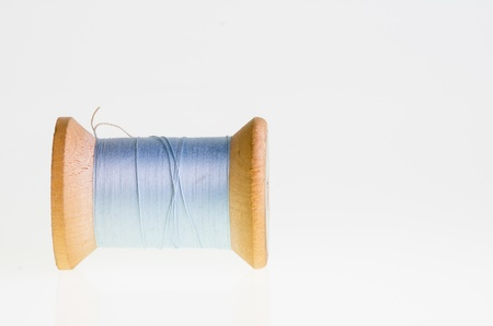 A spool of blue sewing thread isolated on white