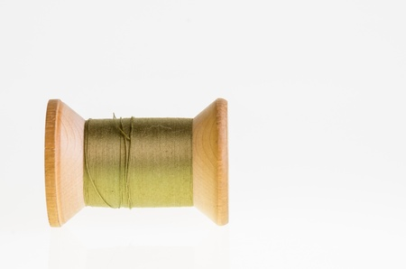 A spool of green sewing thread isolated on white