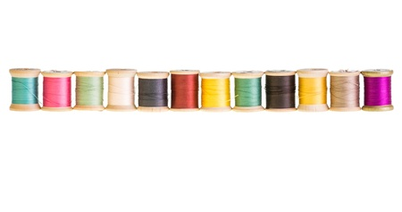 A row of sewing thread spools isolated on white