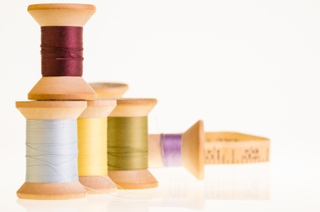 Spools of thread and a measuring tape on white