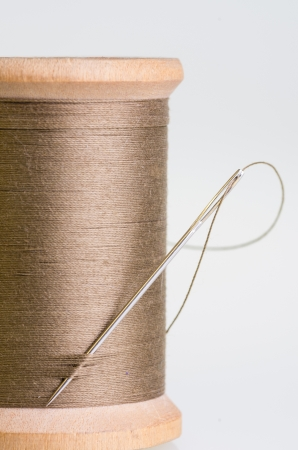 Spool of brown sewing thread with a needle Stock Photo