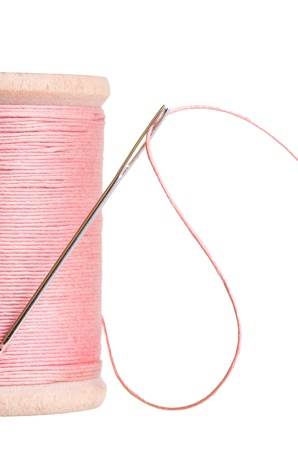 A spool of pink sewing thread with a needle Stock Photo