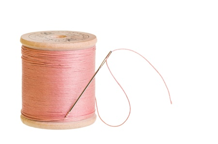 A spool of pink sewing thread with a needle on white