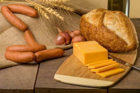 A still life with sausage cheese and bread on a cutting board photo