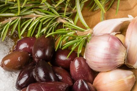 kalamata: Kalamata olives with rosemary garlic cloves and salt ready to prepare Stock Photo