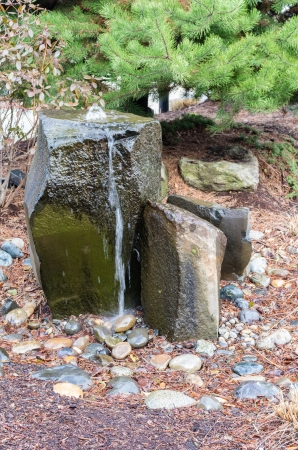 cedars: A rocky bubbling water fountain in a courtyard garden Stock Photo