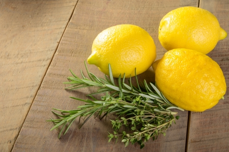 Fresh lemons with rosemary and thyme on a wooden table