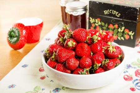Kom verse aardbeien met jam en een recept doos Stockfoto