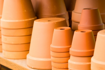 A group of clay pots on a shelf ready to be planted