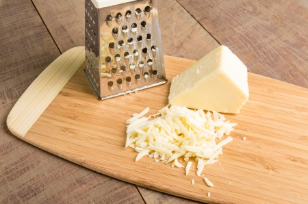 Fresh Parmesan cheese with a metal grater on a cutting board