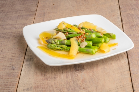 A plate fresh pickled asparagus on wooden table