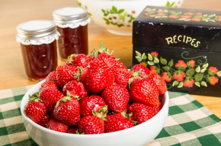 Kom verse aardbeien met potten van jam of gelei Stockfoto